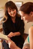 Cosmetólogo Advising Female Client en productos de belleza Imágenes de archivo libres de regalías