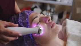 Cosmetólogo con el dispositivo del microdermabrasion que hace la exfoliación de la cara a la mujer joven que miente en el balnear almacen de metraje de vídeo