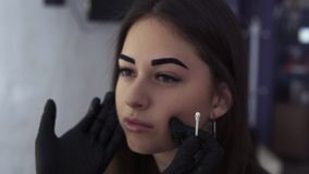 Cosmetólogo en frotaciones negras de la máscara con las cejas de algodón de una mujer de la esponja, estilo la forma Ceja de la c almacen de video