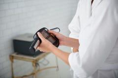 Cosmetólogo en la capa blanca del laboratorio que comprueba el peso de la mujer joven fotografía de archivo libre de regalías