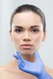 Cosmetólogo en los guantes de goma que tocan la cara de jóvenes Foto de archivo