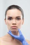 Cosmetólogo en los guantes de goma que tocan la cara de jóvenes Imagen de archivo