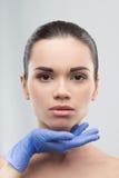Cosmetólogo en los guantes de goma que tocan la cara de jóvenes Fotos de archivo libres de regalías