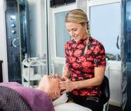Cosmetólogo feliz Giving Face Massage al cliente Imagenes de archivo