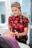 Cosmetólogo Giving Face Massage al cliente en salón Fotografía de archivo libre de regalías