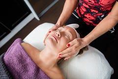 Cosmetólogo Giving Face Massage al cliente en salón Foto de archivo libre de regalías