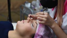 Cosmetólogo profesional que experimenta procedimiento de la extensión de la pestaña Amo y un cliente en un salón de belleza moder almacen de metraje de vídeo