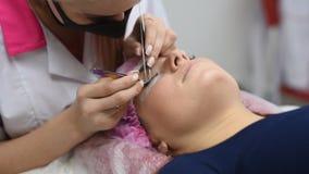 Cosmetólogo profesional que experimenta procedimiento de la extensión de la pestaña Amo y un cliente en un salón de belleza moder metrajes