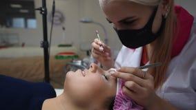 Cosmetólogo profesional que experimenta procedimiento de la extensión de la pestaña Amo y un cliente en un salón de belleza moder almacen de video