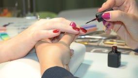Cosmetólogo que aplica clavos polacos a los clavos de las mujeres almacen de metraje de vídeo