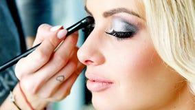 Cosmetólogo que aplica maquillaje a un modelo rubio hermoso metrajes