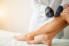 Cosmetólogo que encera una pierna de la mujer que aplica una tira de material sobre la cera caliente imágenes de archivo libres de regalías