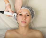 Cosmetólogo que examina la cara de un cliente femenino joven en el salón del balneario el conseguir de rf-elevación en un salón d Imágenes de archivo libres de regalías