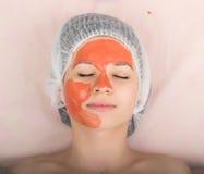Cosmetólogo que examina la cara de un cliente femenino joven en el salón del balneario El cosmetólogo hace la máscara cosmética e Foto de archivo