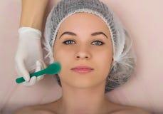 Cosmetólogo que examina la cara de un cliente femenino joven en el salón del balneario El cosmetólogo hace la máscara cosmética e Imagen de archivo