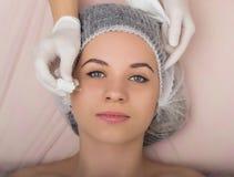 Cosmetólogo que examina la cara de un cliente femenino joven en el salón del balneario el cosmetólogo quita la mascarilla del pac Fotografía de archivo libre de regalías