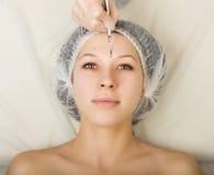 Cosmetólogo que examina la cara de un cliente femenino joven en el salón del balneario limpieza de la cara, cuchara de Una profes Foto de archivo