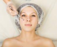 Cosmetólogo que examina la cara de un cliente femenino joven en el salón del balneario limpieza de la cara, cuchara de Una profes Foto de archivo libre de regalías