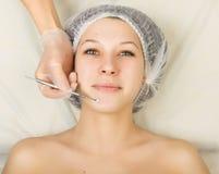 Cosmetólogo que examina la cara de un cliente femenino joven en el salón del balneario limpieza de la cara, cuchara de Una profes Fotografía de archivo libre de regalías