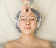 Cosmetólogo que examina la cara de un cliente femenino joven en el salón del balneario limpieza de la cara, cuchara de Una profes Imágenes de archivo libres de regalías