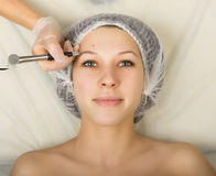 Cosmetólogo que examina la cara de un cliente femenino joven en el salón del balneario Maquillaje permanente, tatuaje en un salón Fotografía de archivo
