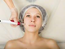 Cosmetólogo que examina la cara de un cliente femenino joven en el salón del balneario mesotherapy fraccionario en un salón de be Foto de archivo libre de regalías