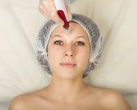Cosmetólogo que examina la cara de un cliente femenino joven en el salón del balneario mesotherapy fraccionario en un salón de be Imagen de archivo