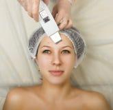 Cosmetólogo que examina la cara de un cliente femenino joven en el salón del balneario persona de la limpieza ultrasónica profesi Foto de archivo
