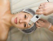 Cosmetólogo que examina la cara de un cliente femenino joven en el salón del balneario persona de la limpieza ultrasónica profesi Fotos de archivo libres de regalías