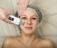 Cosmetólogo que examina la cara de un cliente femenino joven en el salón del balneario persona de la limpieza ultrasónica profesi Imagen de archivo libre de regalías