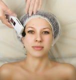 Cosmetólogo que examina la cara de un cliente femenino joven en el salón del balneario persona de la limpieza ultrasónica profesi Imagenes de archivo