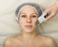 Cosmetólogo que examina la cara de un cliente femenino joven en el salón del balneario persona de la limpieza ultrasónica profesi Fotografía de archivo libre de regalías
