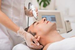Cosmetólogo que hace masaje del facial de la cavitación del ultrasonido Foto de archivo