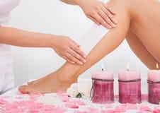 Cosmetólogo Waxing la pierna de una mujer Foto de archivo