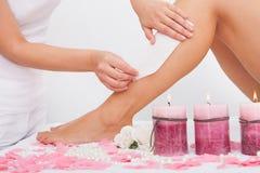 Cosmetólogo Waxing la pierna de una mujer Imágenes de archivo libres de regalías