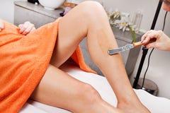 Cosmetólogo Waxing la pierna de una mujer Imagen de archivo libre de regalías