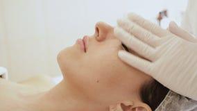 Cosmet?logo que hace el masaje de caras femeninas Primer de la muchacha de la cara del masaje almacen de video
