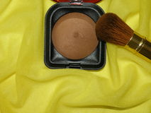 Cosmetic. Brown powder and brush on the yellow fabric Royalty Free Stock Photo