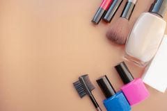 Cosmetic accessories. Brush, blush, lipstick, cream, nail polish on a yellow, cream background royalty free stock image