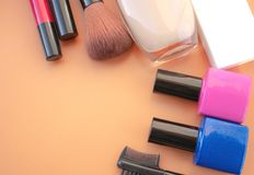 Cosmetic accessories. Brush, blush, lipstick, cream, nail polish on a yellow, cream background royalty free stock photography