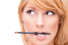 Cosmetic artistry. A beautiful young woman wearing  biting a makeup brush Stock Images