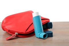 Cosmetic bag with asthma inhalers. On wooden table Royalty Free Stock Images