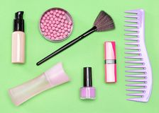 Cosmetic bag must-haves. Modern woman essentials: foundation, blush, lipstick, perfume, nail polish, comb. Cosmetic bag must-haves. Top view, flat lay Stock Images