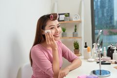 Cosmetic beauty procedures and makeover concept. Woman in hair curlers beautiful young woman using cotton pads at home stock image