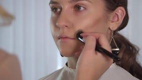 Cosmetic beauty procedures. Makeup artist applying with brush eyeshadow on female eye, woman putting shadow powder on