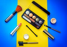 Cosmetic  beauty products for make-up on bright colorful background. – eye shadows, brushes, lipstick, face cream and highlighter base in small jars Stock Image