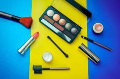 Cosmetic  beauty products for make-up on bright colorful background. – eye shadows, brushes, lipstick, face cream and highlighter base in small jars Stock Photo