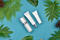 Cosmetic bottle containers on green herbal leaves background, Blank label for branding mock-up. Cosmetic bottle containers on green herbal leaves background royalty free stock photos