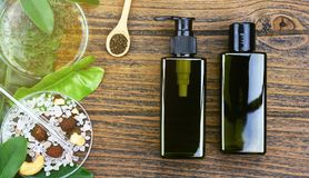 Cosmetic bottle containers with green herbal leaves, Blank label package for branding mock-up. Cosmetic bottle containers with green herbal leaves, Blank label stock photo