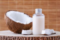 Cosmetic bottle and fresh organic coconut for skincare, natural background. Cosmetic bottle and fresh organic coconut for skincare, natural brown background Stock Photos